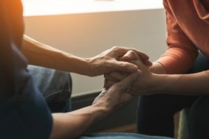 close up of man holding woman's hands in support during substance abuse treatment programs Nevada