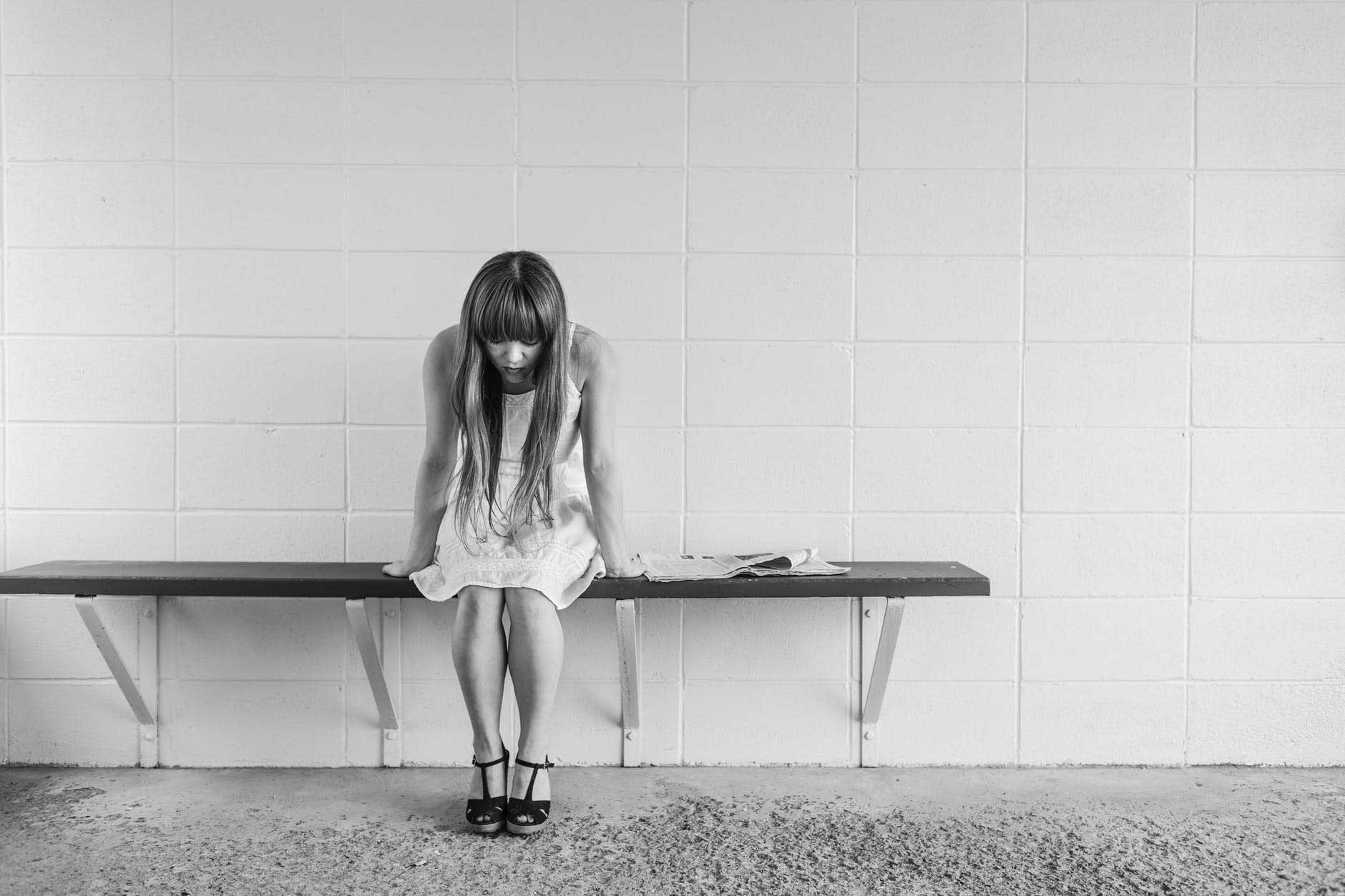 black and white young woman in dress on bench illustrates long terms psychological and physical effects of drug abuse