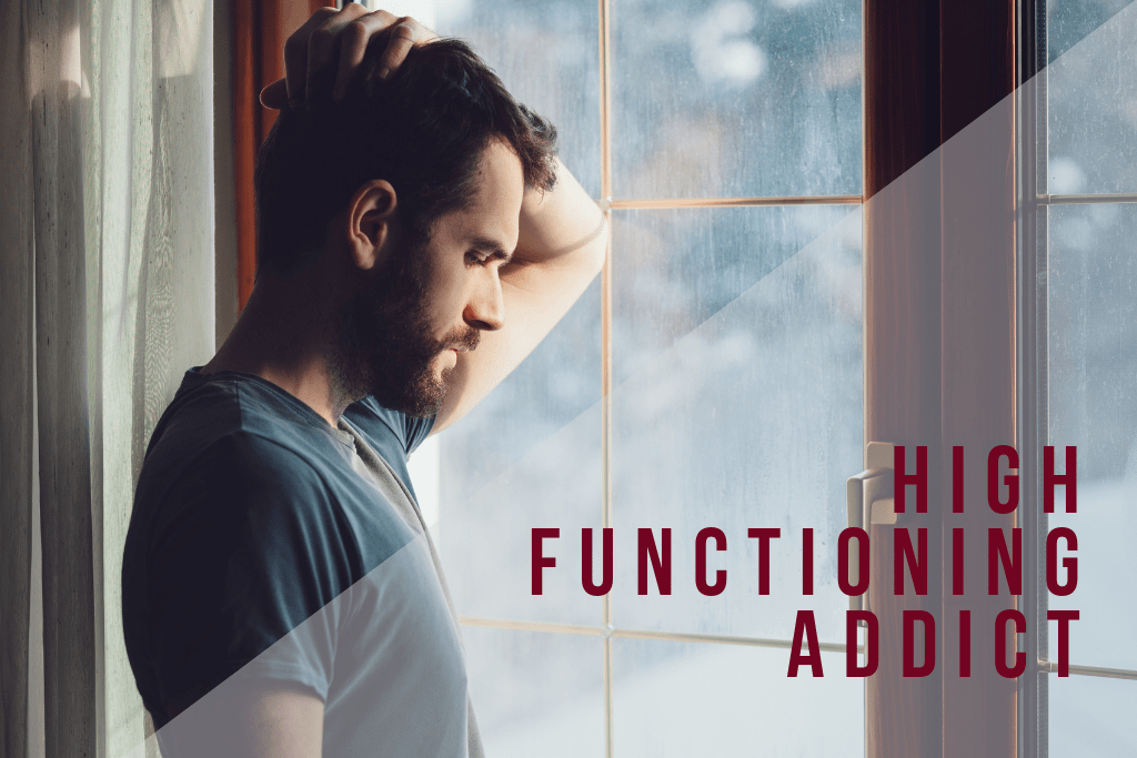 bearded man at window with hands on head illustrating the definition of a high functioning addict