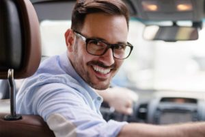 man wearing glasses in driver's seat looking back at camera smiling as he remembers intensive outpatient programs