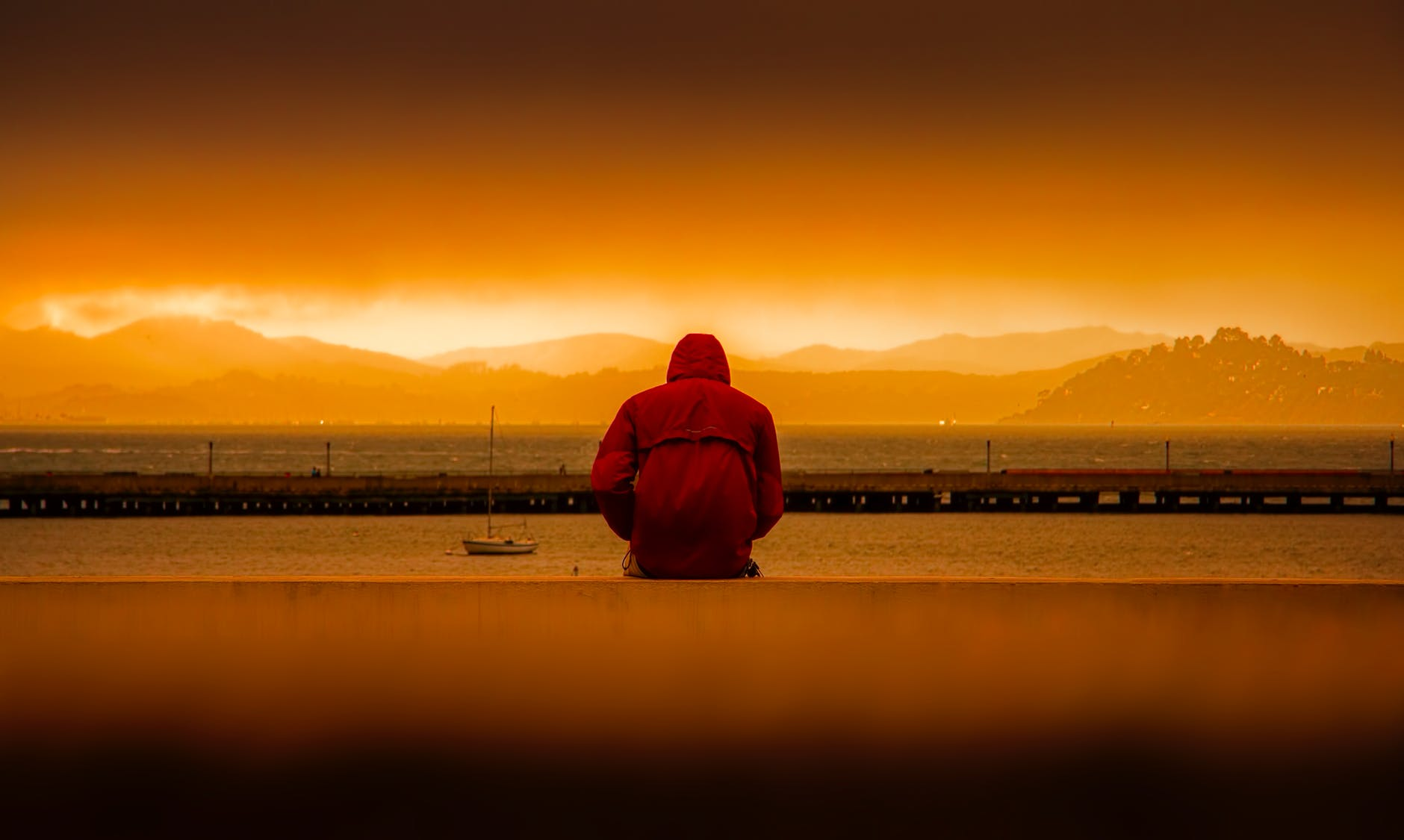 rear view of person in hooded jacket overlooking the sea at sunrise illustrating suicide and self harm with addiction
