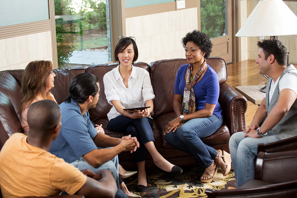 therapy circle sitting on couches discussing what is partial hospitalization